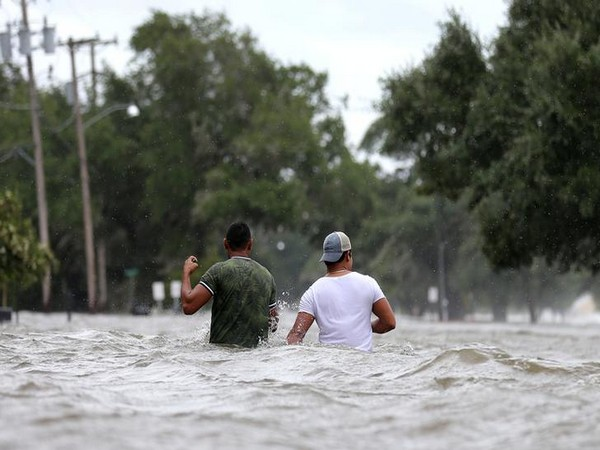 People wade through a flooded street after Hurricane Barry in Mandeville